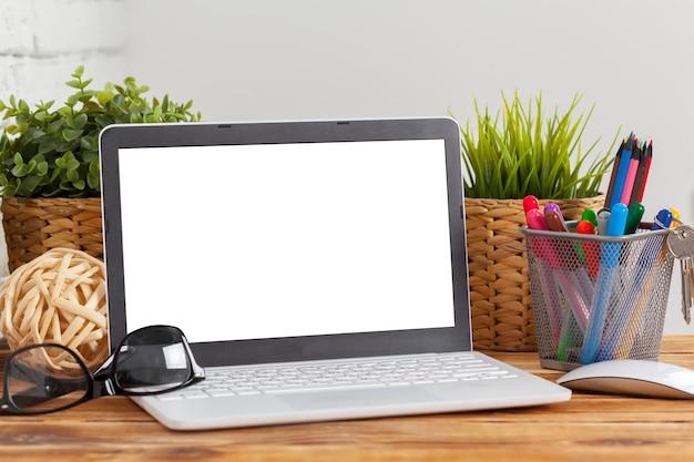 作業スペース、木製のテーブルの上のノートパソコンの空白の画面、 Premium写真