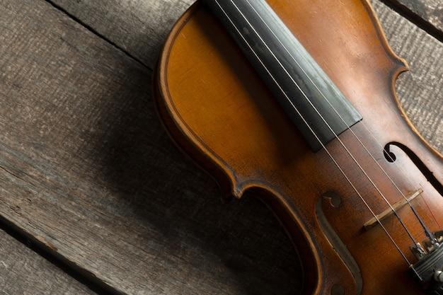 木製の織り目加工テーブルの上のバイオリン Premium写真