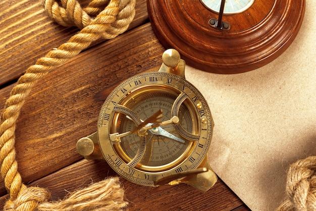 コンパスと木製のテーブルの上にロープ。閉じる Premium写真