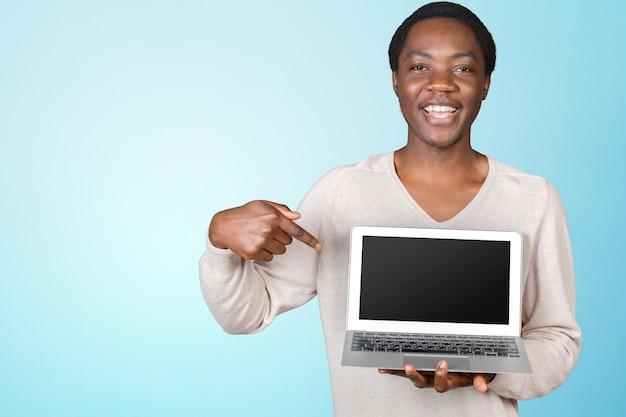 ラップトップと幸せな笑みを浮かべてハンサムな男 Premium写真