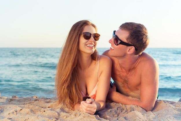 ビーチで楽しんでサングラスで幸せなカップル Premium写真