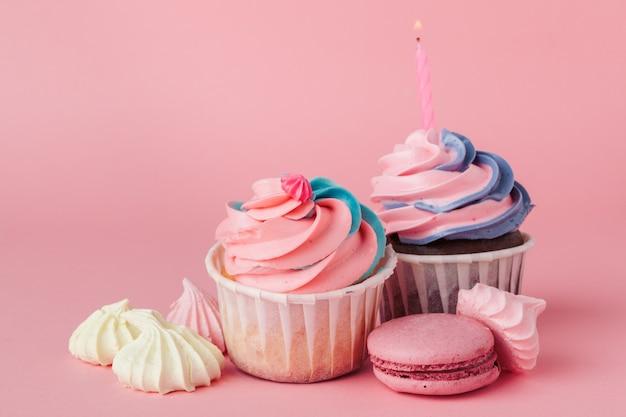 明るいピンクの背景においしいカップケーキをクローズアップ Premium写真