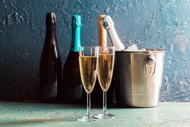 Бутылка шампанского в ведре со льдом и бокалами шампанского Premium Фотографии