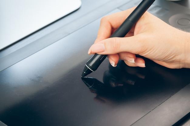 Женщина вручает графическому дизайнеру работая на цифровой таблетке Premium Фотографии