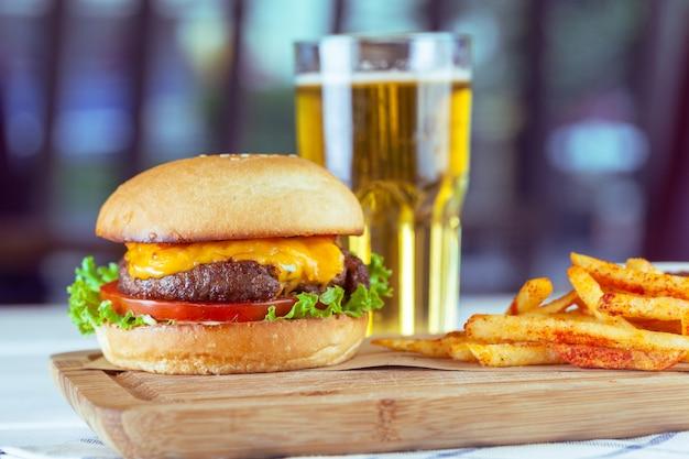 木製のテーブルにハンバーガーとフライドポテト Premium写真