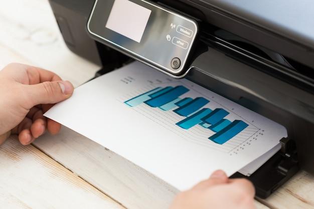 コピーを作る人間の手。プリンターでの作業 Premium写真