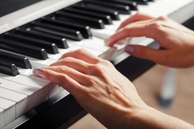 Крупным планом руки, играть на пианино. музыка и концепция хобби Premium Фотографии