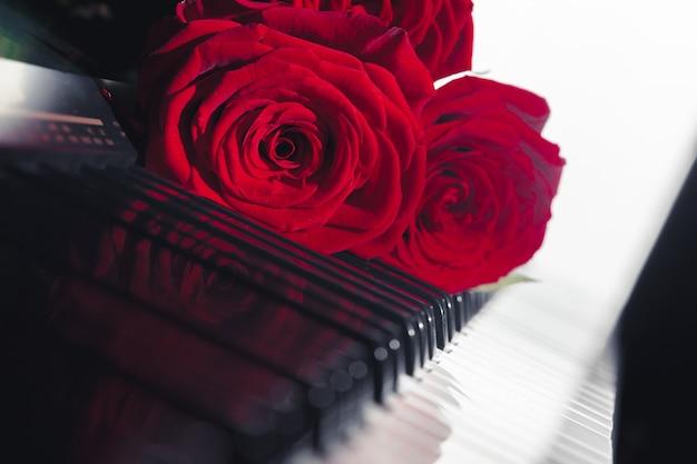 ピアノの鍵盤に赤いバラ Premium写真
