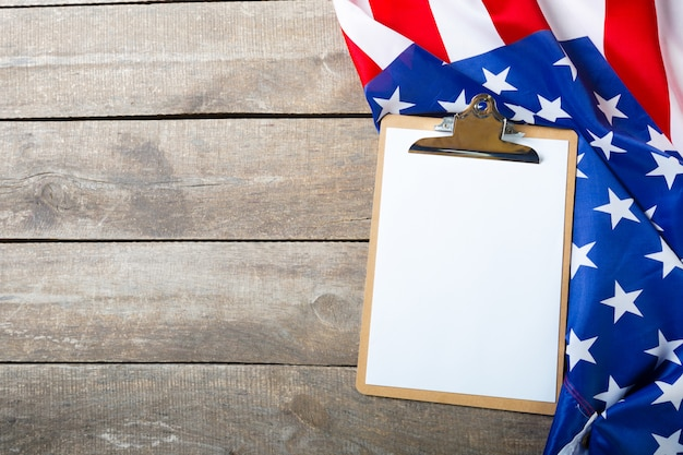 空白のクリップボードと木製の背景にアメリカ国旗 Premium写真