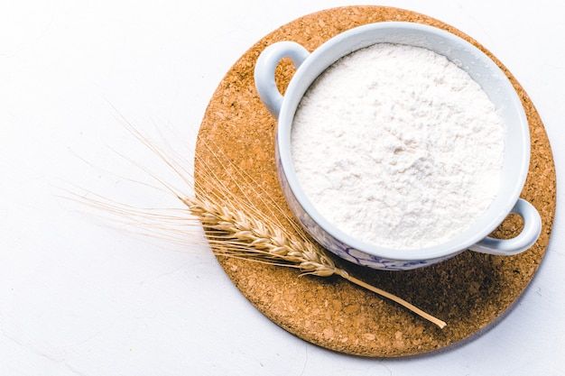 Цельная мука в миске с колосьями пшеницы на белом фоне Premium Фотографии