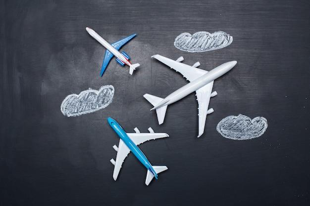 黒板と矢印の図面上のおもちゃの飛行機 Premium写真