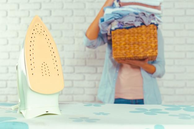 アイロン台に洗濯物の巨大な山をもたらす主婦 Premium写真