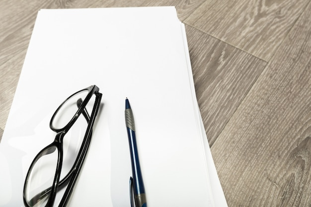 空白のノートブックと木製のテーブルに眼鏡の鉛筆 Premium写真