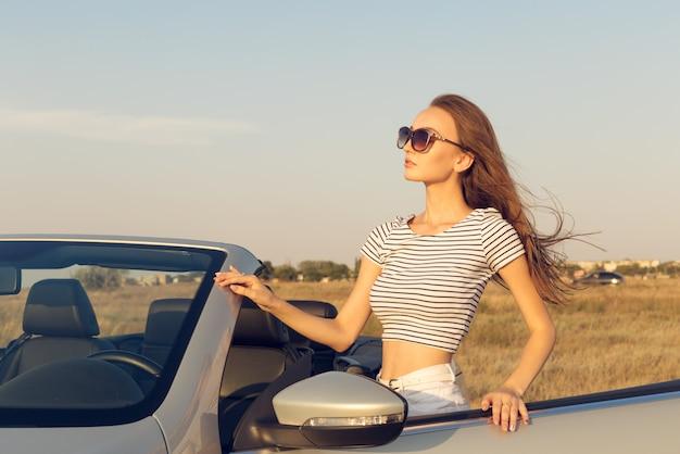 コンバーチブル車の近くの魅力的な若い女性 Premium写真