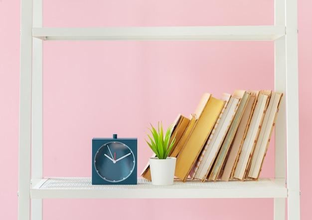 本とピンクの壁に植物の白い本棚 Premium写真