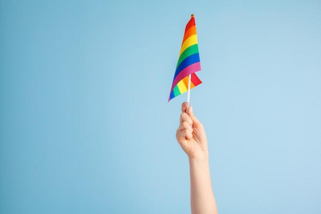 Гей флаги в женской руке на сером фоне Premium Фотографии