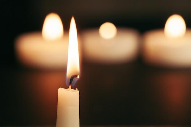 Одна горящая свеча, изолированная на черном фоне Premium Фотографии