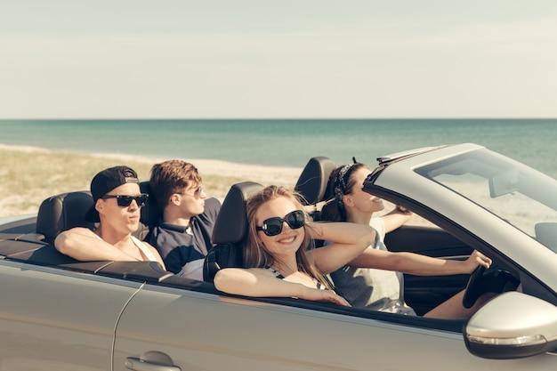Улыбающиеся друзья за рулем автомобиля возле моря и с удовольствием Premium Фотографии