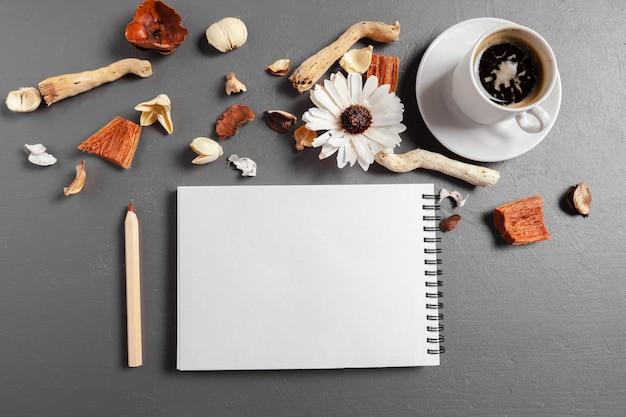 ペン、コーヒー、テーブルの上の花とノート Premium写真