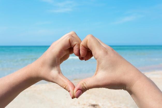 Руки женщины, делая форму сердца на пляже Premium Фотографии