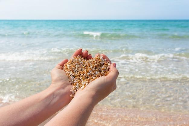 Песок в руке с формой сердца, на берегу моря Premium Фотографии