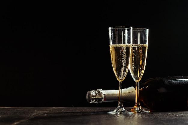 シャンパンと暗い背景上のグラスのボトル Premium写真