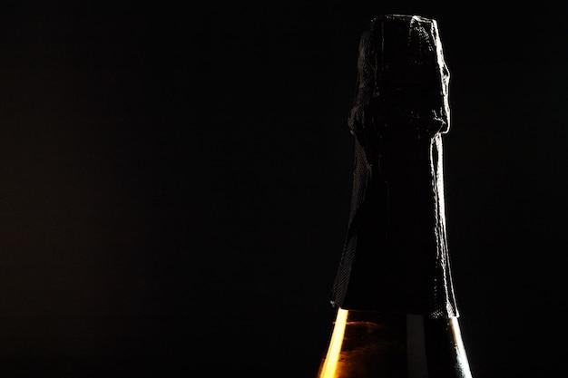 黒い背景にシャンパンのボトル。 Premium写真