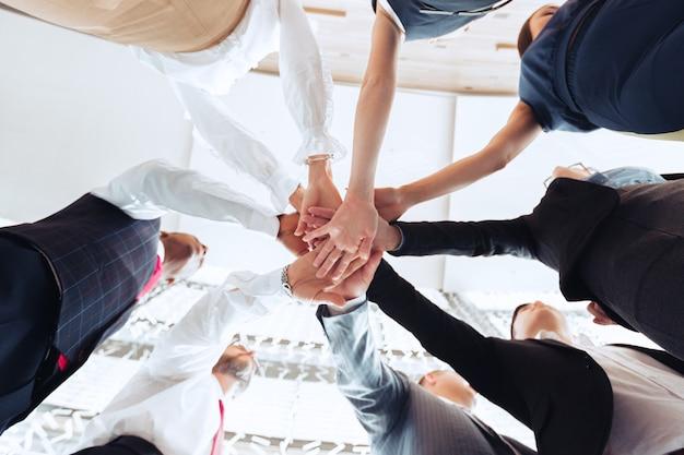互いの上に手を置くビジネスマンのグループのクローズアップ Premium写真