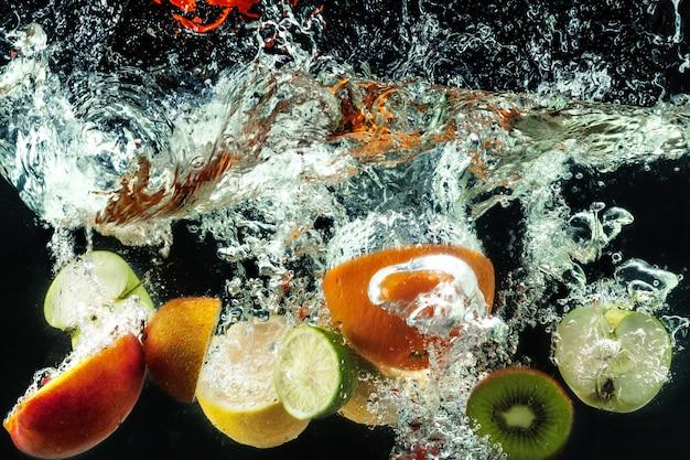 多くの果物が水の中に飛び散る Premium写真