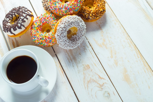 ドーナツと白いウッドの背景上のコーヒー。 Premium写真