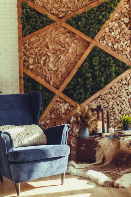 ニットベージュの枕とモダンなインテリアの青いアームチェア Premium写真