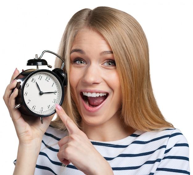 若い笑顔の女性は黒い時計を保持します Premium写真
