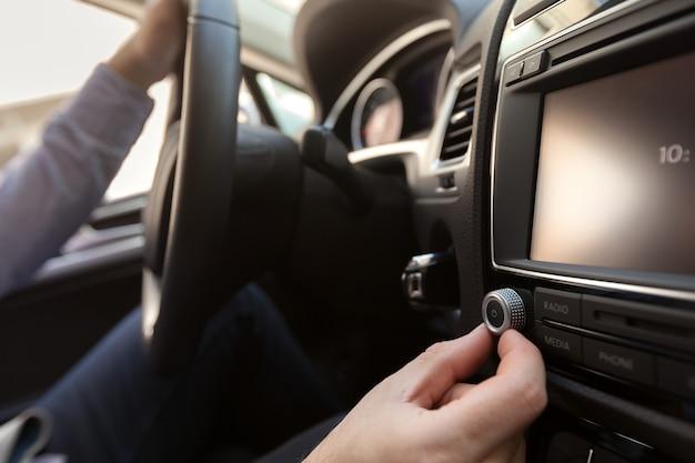 Рука нажмите кнопку питания, чтобы включить автомобильную стереосистему Premium Фотографии