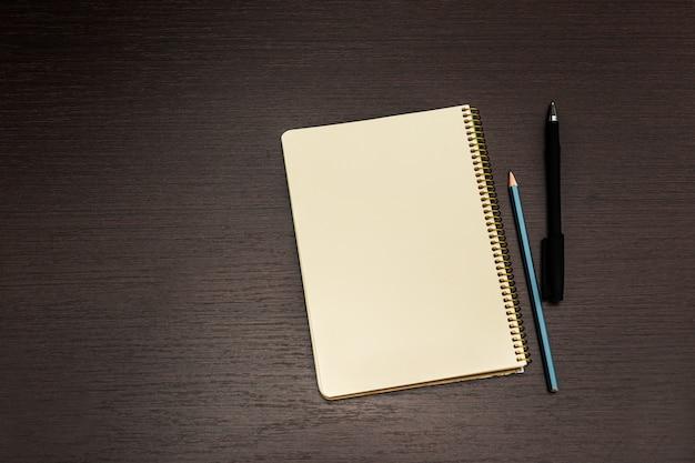 空白のページと木製の机の上のペンでノートブックを開く Premium写真