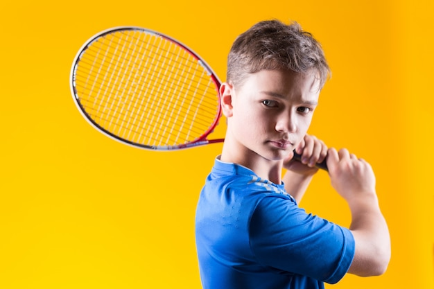 明るい黄色の壁に若い男の子のテニスプレーヤー Premium写真