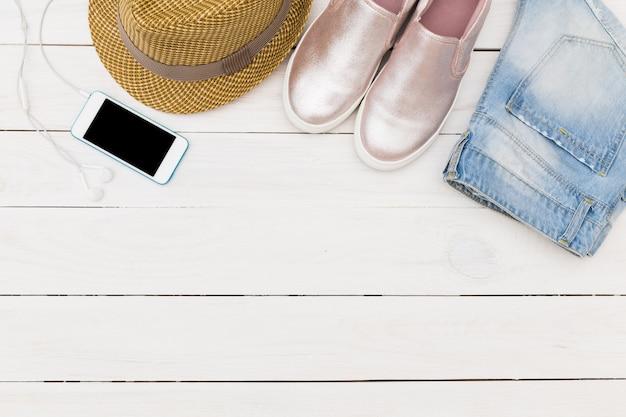 木の床にデニムのショートパンツ、麦わら帽子、靴 Premium写真