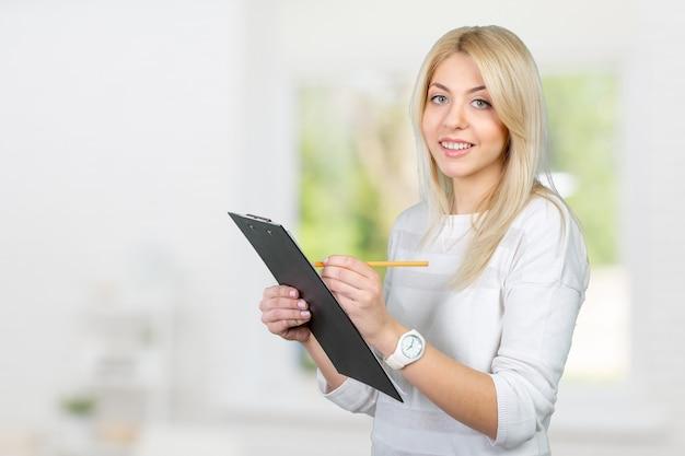Блондинка предприниматель пишет заметки в буфер обмена Premium Фотографии