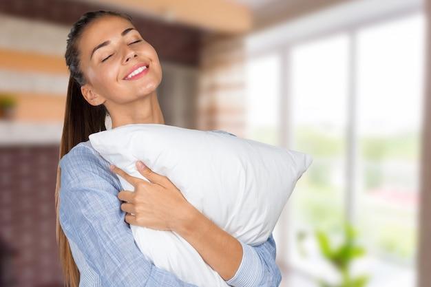 枕と若い美しい女性の肖像画 Premium写真
