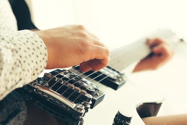 エレキギターを弾く男 Premium写真