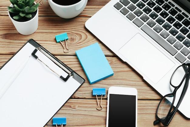 木製のオフィスデスクテーブルとアングルビューでブラックコーヒーを扱うための機器 Premium写真