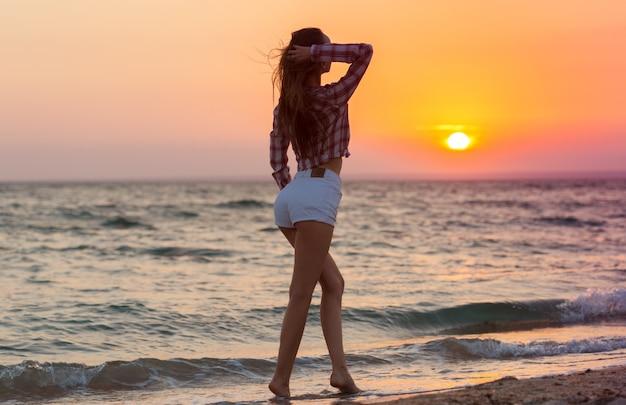 夏を楽しんでビーチで幸せな屈託のない女性 Premium写真