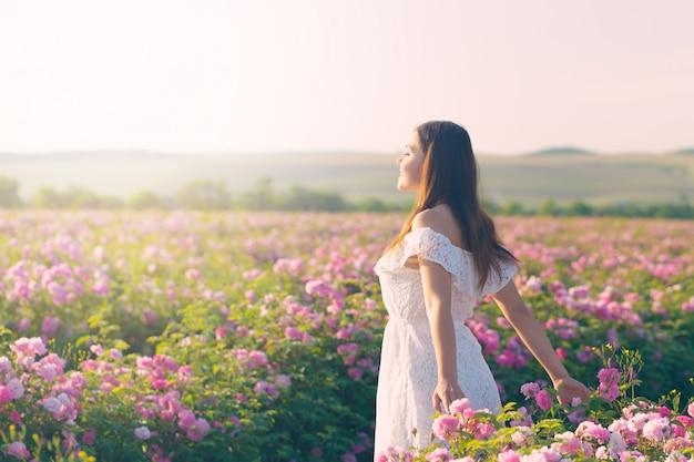 美しい若い女性が庭のバラに近いポーズします。 Premium写真