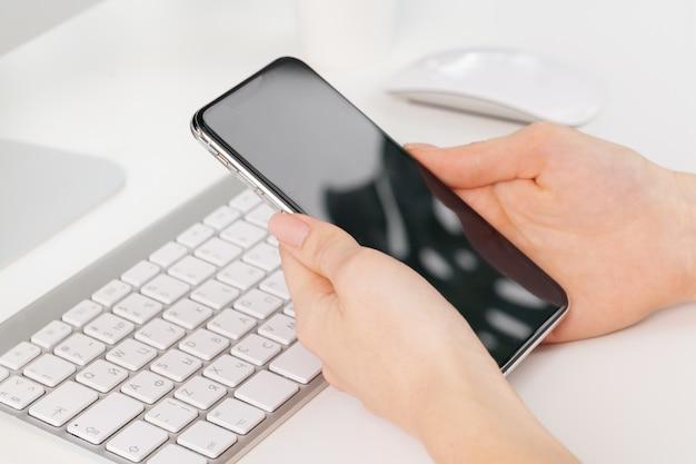 オフィスのテーブルでスマートフォンを使用して女性の手のクローズアップ Premium写真
