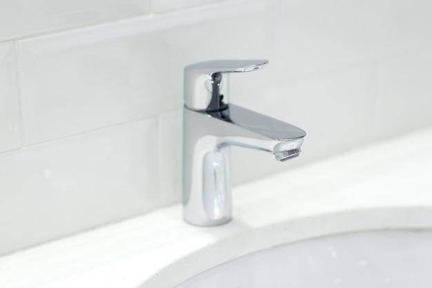 Хромированный кран на керамической раковине в ванной комнате крупным планом Premium Фотографии