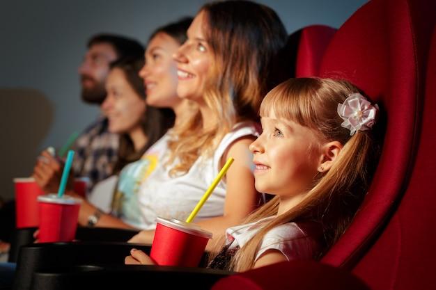 ポップコーンとドリンクの映画館に座っている友人のグループ Premium写真