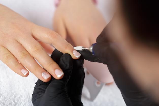 ビューティーサロンでマニキュアを受ける女性の手 Premium写真