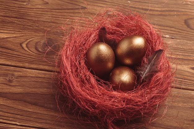 Золотые яйца на деревянный стол Premium Фотографии