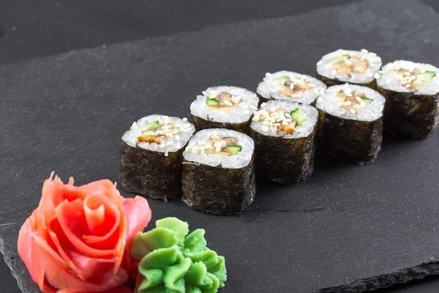 日本のレストラン、黒いスレートプレートの寿司ロール。 Premium写真