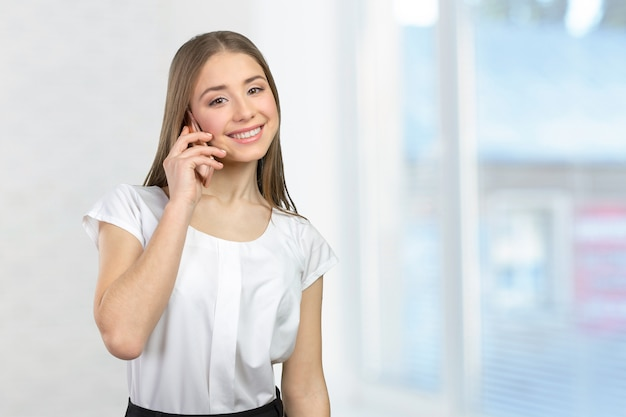 Молодая элегантная женщина разговаривает по мобильному телефону Premium Фотографии