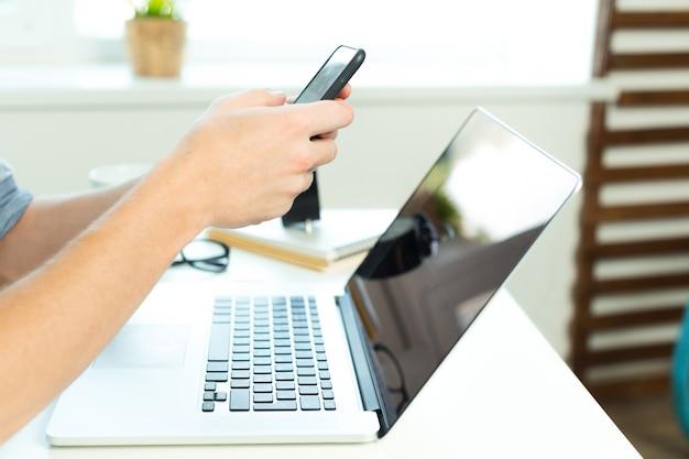 Молодой студент работает на своем ноутбуке дома Premium Фотографии